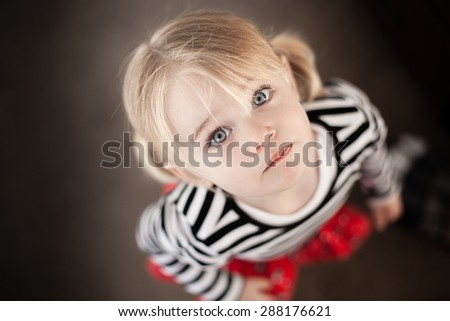 Cute little toddler looking up at the camera - stock photo