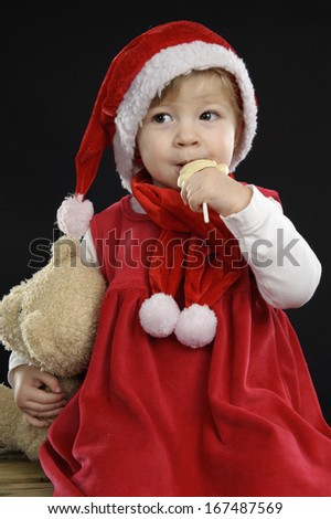 Cute little toddler with christmas hat eating a chocolate lolly on black background - stock photo