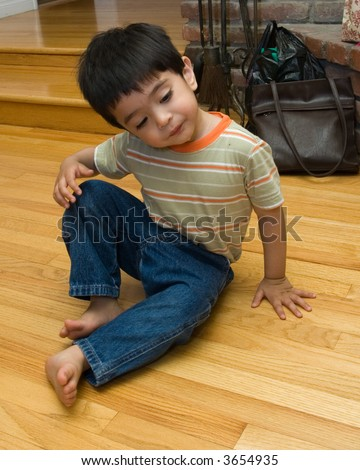 Cute little two year old boy toddler sitting on hardwood floor with a cute expression at home