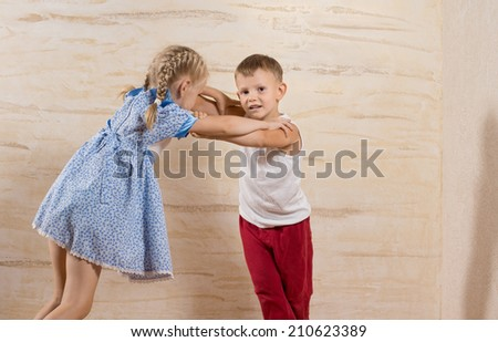Cute Little White Kids Playing at Home Isolated on Light Brown Wooden Walls - stock photo