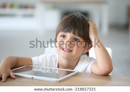 Cute little 4-year-old girl playing with tablet - stock photo