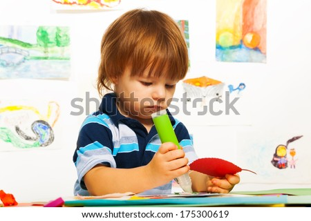Cute little 2 years old boy in the art  glue color cardboard leaf - stock photo