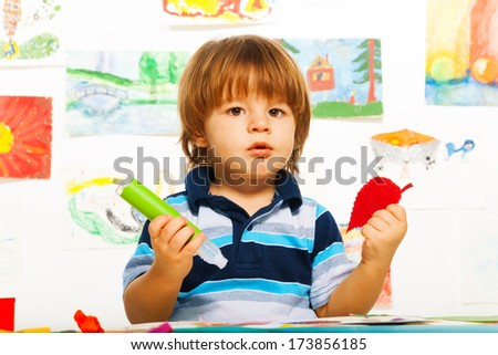Cute little 2 years old boy in the art  glue color paper leaf - stock photo