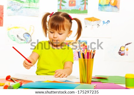 Cute little 3 years old girl in yellow shirt and pony tails draw with pencil in the art class with images on the wall - stock photo