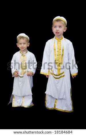 Cute little 3yr and 5yr old boys wearing traditional Arabian thobes for the purpose of asking for Ramadan treats. - stock photo