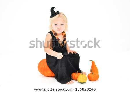 Cute littlest witch sitting on a pumpkin for Halloween. - stock photo