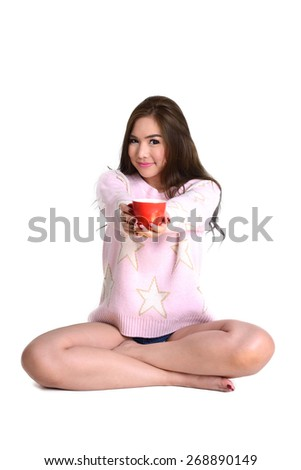 Cute long hair woman in pink sweater sit on the floor and put red coffee cup in her two hands forward on white background.