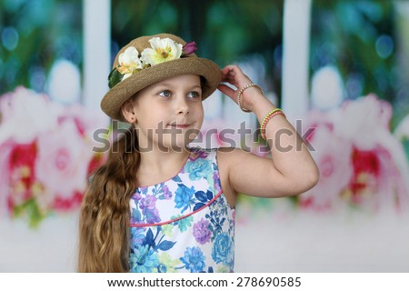 Cute long haired girl adjusts flowers decorated hat on her head - children beauty and fashion concept - stock photo