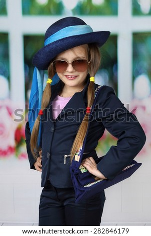 Cute long haired girl in blue hat and sunglasses - children beauty and fashion concept