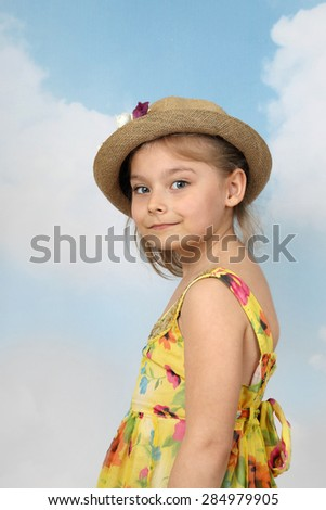 Cute long haired girl in flowers decorated hat half turn portrait on blue sky background - children beauty and fashion concept - stock photo