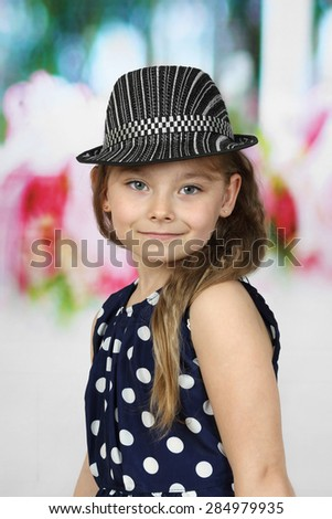 Cute long haired girl  in polka-dot dress and  hat portrait - children beauty and fashion concept - stock photo