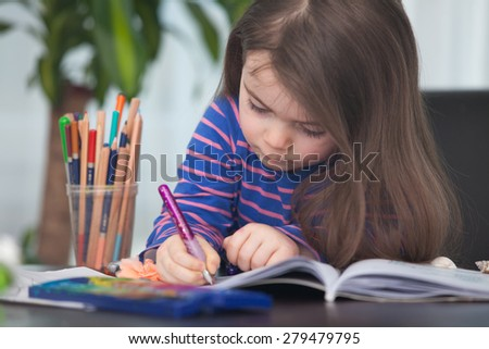 Cute long-haired hard-working girl writing on notebook her homework for elementary school, at her desk equipped with colored pencils and watercolor painting set
