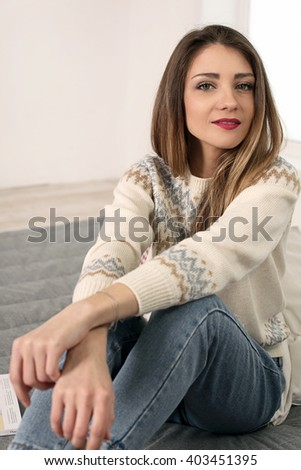 cute long-haired young woman in sweater and jeans ripped sitting on the floor looking thoughtfully dreamily aside