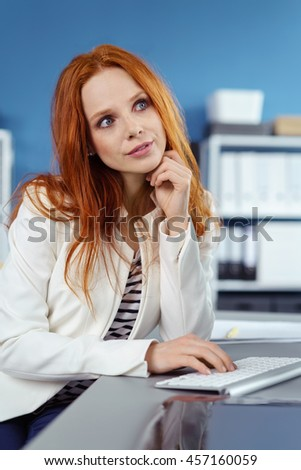 Cute long red haired young woman in white blazer and striped shirt at keyboard with fingers under chin in daydreaming expression - stock photo