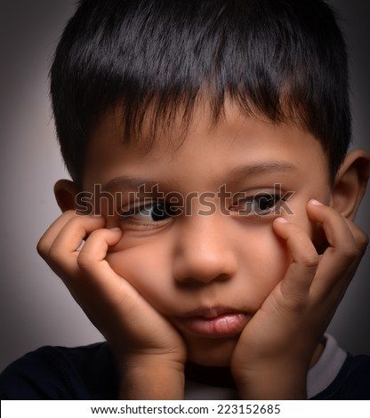 Cute looking boy in sad state of mind. - stock photo