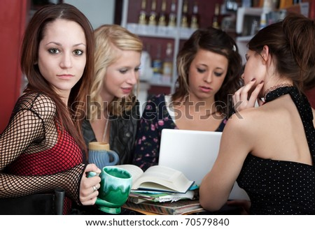 Cute looking young girl with her friends in a cafe discussing a project