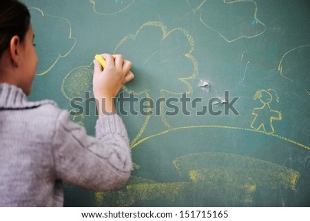 Cute lovely school children at clasroom having education activities drawing tree - stock photo
