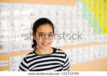 Cute lovely school children at class with periodic table of the elements - stock photo