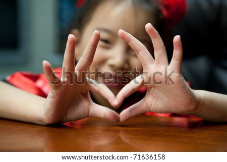 cute lovely sweet asian kid girl with love symbol in home background - stock photo