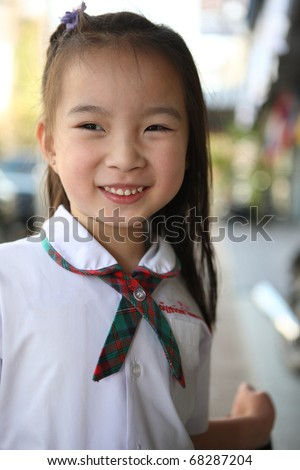 cute lovely sweet little asian girl with smiling face in town background - stock photo