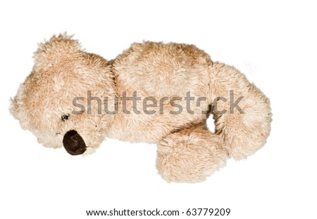 Cute, lovely teddy bear lying on the floor, isolated - stock photo