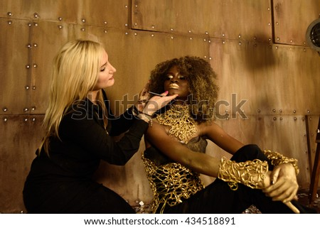 Cute makeup artist painting lips to model at photo shoot on floor in bright gold studio - stock photo