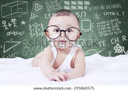 Cute male baby looking on the camera while wearing glasses, shot with a doodles background on the blackboard - stock photo