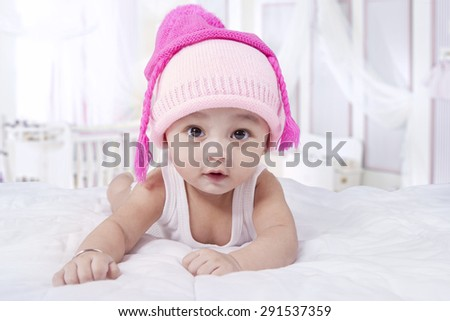 Cute male infant lying on bed while wearing hat and look at the camera in the bedroom - stock photo