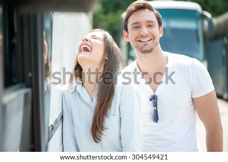Cute man and woman are making fun in their trip. They are standing near a public transport and laughing. The girl closed her eyes with joy. He boyfriend is looking at the camera happily - stock photo