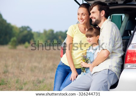 Cute married couple and their daughter are sitting on car trunk. They are relaxing in the nature and smiling. The parents are embracing their child and looking forward. Copy space in left side - stock photo