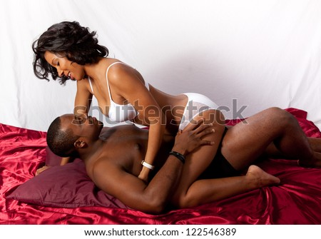 Cute married couple in sexual foreplay together in their underwear, he is supine and she is sitting on him and looking into his eyes lovingly - stock photo