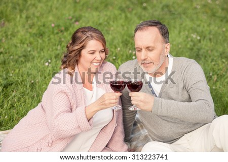 Cute mature husband and wife are making picnic in park. They are lying on grass and drinking wine. The man and woman are looking at glasses and smiling