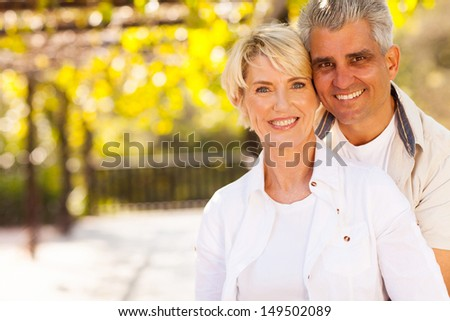 cute mid age couple outdoors looking at the camera - stock photo