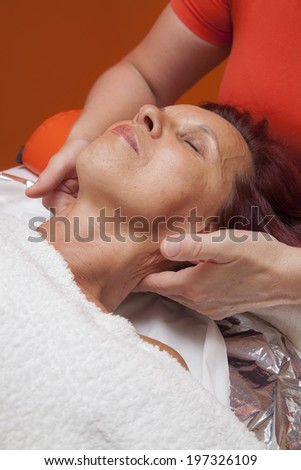 Cute mid aged woman receiving a professional therapeutic facial massage and lymphatic drainage, while lying on a towel in a award-winning health massage center, series of various techniques  - stock photo