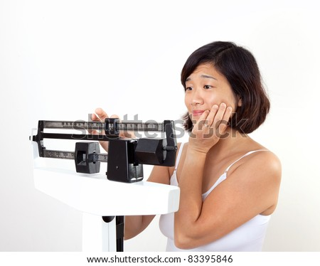 Cute middle age woman on vertical weight scale looking disappointed at her current weight - stock photo