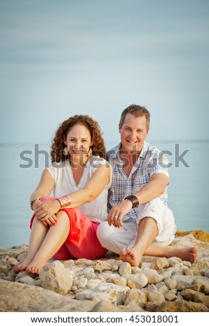Cute middle aged couple sitting on rocks at the beach portrait - stock photo