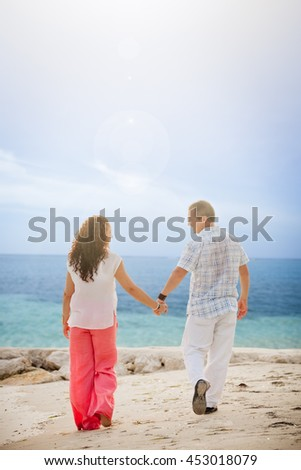 Cute middle aged couple walking and holding hands on the beach in Jamaica - stock photo