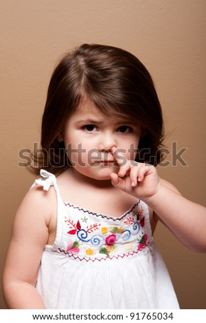 Cute mischievous toddler girl with finger in her nose fishing for boogers snot, on brown.
