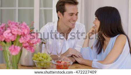 Cute mixed couple enjoying wine and fruit together