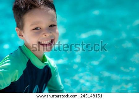 Cute mixed race Asian Caucasian boy happily plays in a backyard swimming pool in the summer sun - stock photo