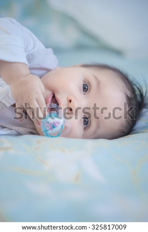 Cute mixed race Asian Caucasian 6 month old baby boy sucking a dummy and smiling plays inside on a bed - stock photo