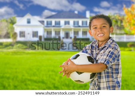 Cute Mixed Race Boy Holding Soccer Ball In Front of Beautiful House. - stock photo