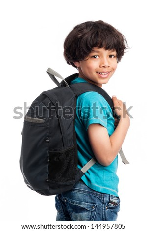 Cute mixed race boy walking away with rucksack on his back. - stock photo