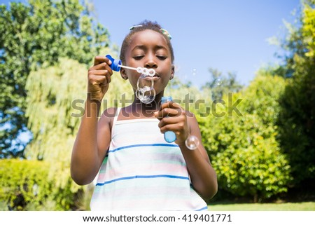 Cute mixed-race girl smiling and playing with bubbles on a park