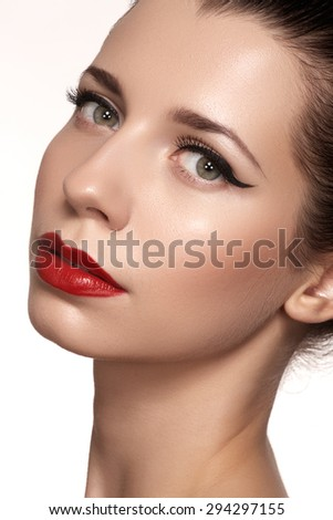 Cute model face with bright classical evening make-up, eyeliner on eyes, red lipstick, purity skin on white background - stock photo