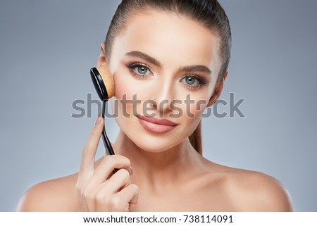 Cute model with brown hair fixed behind, clean fresh skin, big eyes and naked shoulders posing at gray studio background and looking at camera, close up, holding make up brush.