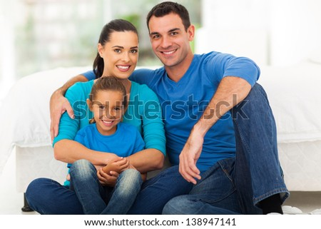 cute modern family of three sitting on bedroom at home - stock photo