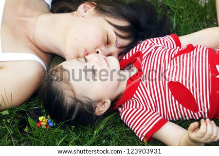 Cute mom and daughter relaxing on the lawn - stock photo