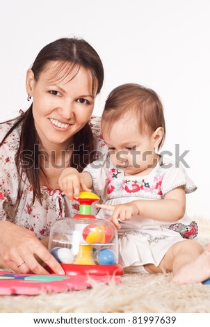 cute mom and her baby playing on carpet