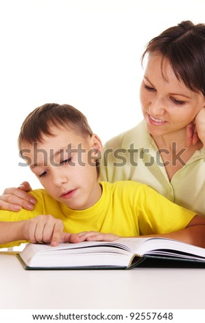 cute mom reading with son at table - stock photo